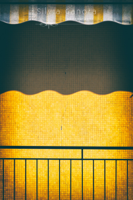 Abstract shot of a sunshade and its shadow on a yellow wall - ©Silvia Ganora Photography - All Rights Reserved