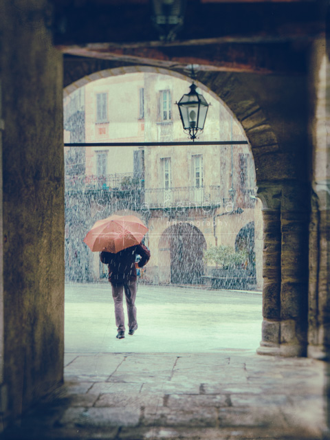 Man framed in an archway walking away from camera holding an umbrella on a snowy day. - ©Silvia Ganora Photography - All Rights Reserved
