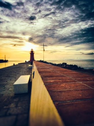 Lighthouse at the end of a promenade in the sunset light - ©Silvia Ganora Photography - All Rights Reserved