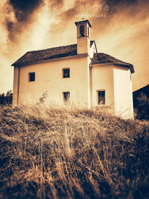 Split toned shot of a little country church with tall grass slope in front of it and dramatic sky - ©Silvia Ganora Photography - All Rights Reserved