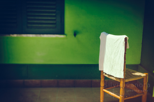 T-shirt left out to dry on a straw chiar. Green wall with window behind - ©Silvia Ganora Photography - All Rights Reserved