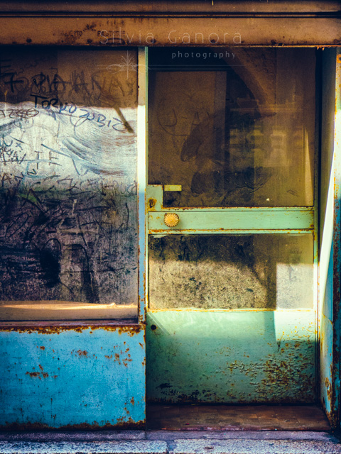 Dirty and decayed shop door and window with writings and sunlight©Silvia Ganora Photography - All rights reserved